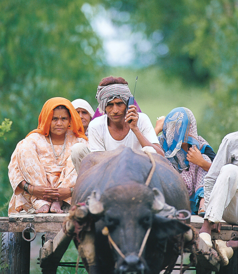 Villager ( farmer ) with his family sitting on a Bullock Cart and Talking on Mobile Phone, in Delhi, India